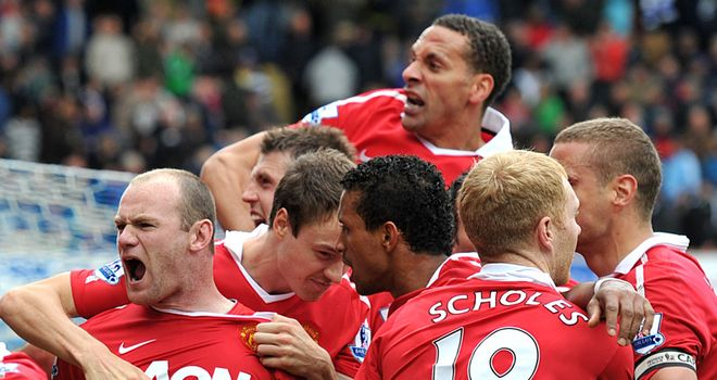 Rooney is mobbed by his team-mates after scoring the penalty