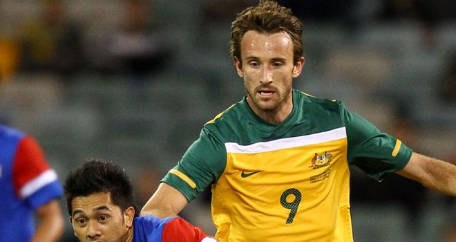 Josh Kennedy tangles for the ball in Australia's 5-0 win over Malaysia