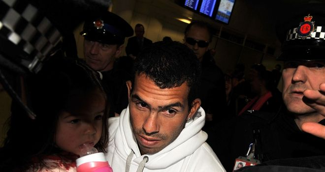 Carlos Tevez: Mobbed as he arrives back in England