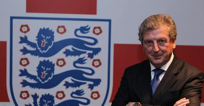 Roy Hodgson poses with the England crest - the famous Three Lions - after being unveiled as manager on Tuesday.