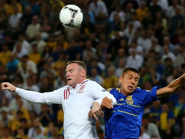 Rooney and Khacheridi go up for a header.