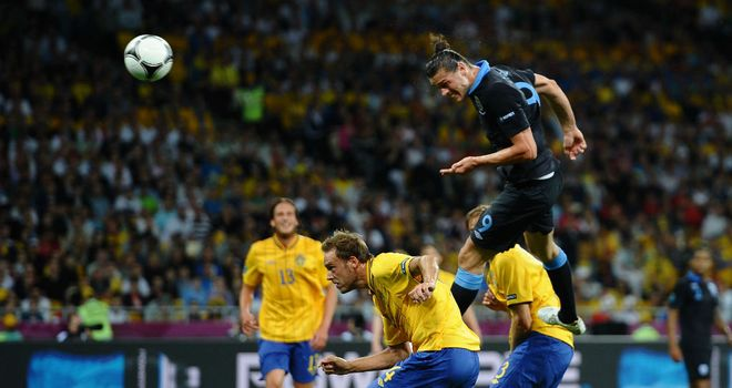 Andy Carroll heads the opener against Sweden. Can he keep Wayne Rooney out of the England team?