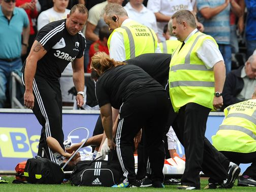 Neil Taylor is loaded onto the stretcher