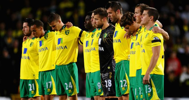 Norwich City's players honour the memory of John Bond with a minute's silence