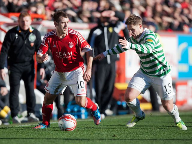 Niall McGinn and Kris Commons battle for the ball