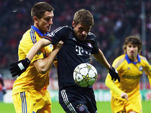 Artem Radkov and Thomas Muller battle for the ball