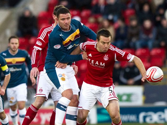 Michael Higdon battles for the ball with Gavin Rae