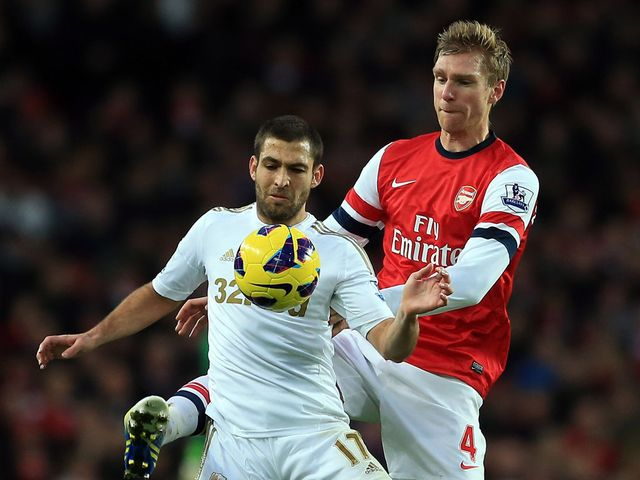 Itay Shechter holds off Per Mertesacker