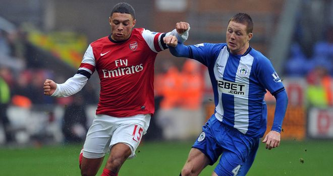 Alex Oxlade-Chamberlain (left) holds off Wigan's James McCarthy