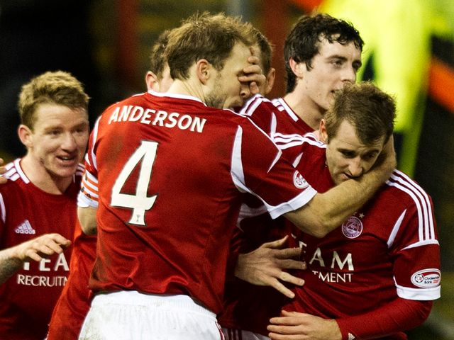 Niall McGinn is mobbed after scoring