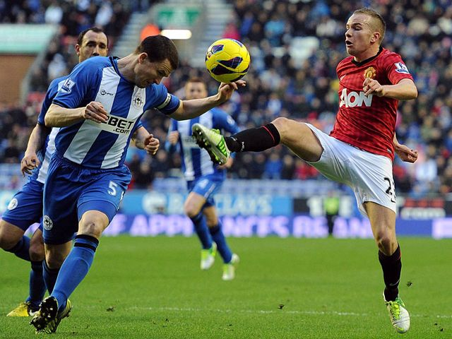 Gary Caldwell and Tom Cleverley go for the ball