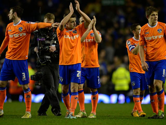 Oldham players applaud their fans after defeat at Everton