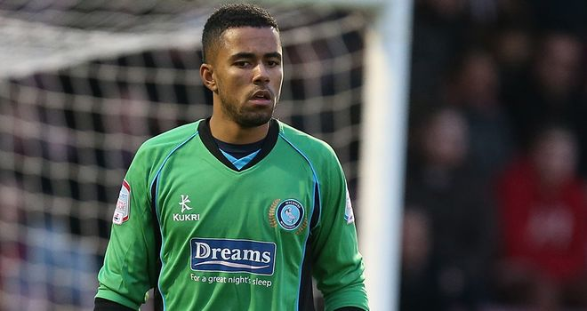 A young Gillingham fan is led away after Wycombe goal keeper Jordan Archer was jumped on during Priestfield clash