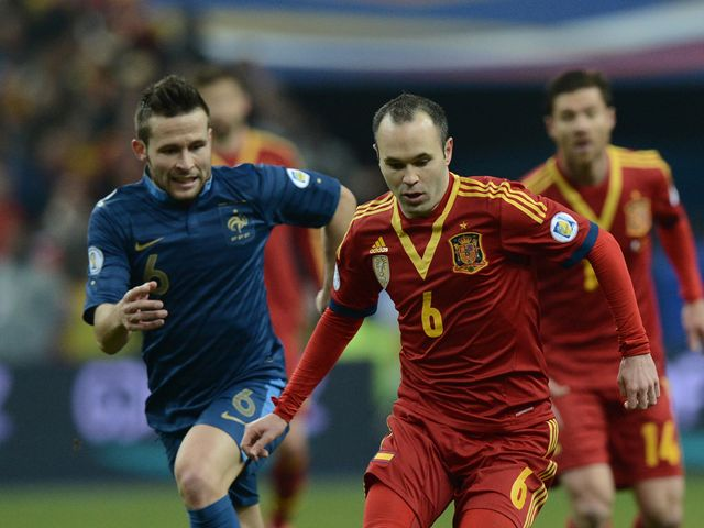 Andres Iniesta holds off France's Yohan Cabaye