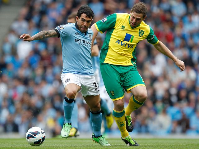 Carlos Tevez holds off Grant Holt