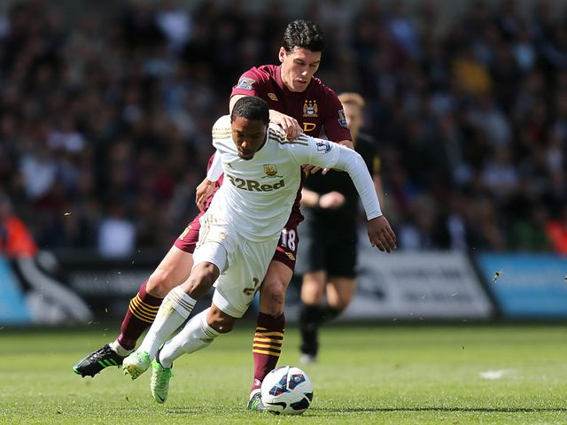 Jonathan de Guzman and Gareth Barry battle for the ball.