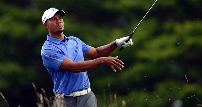 Tiger Woods chops out of the dense rough after a poor opening tee shot
