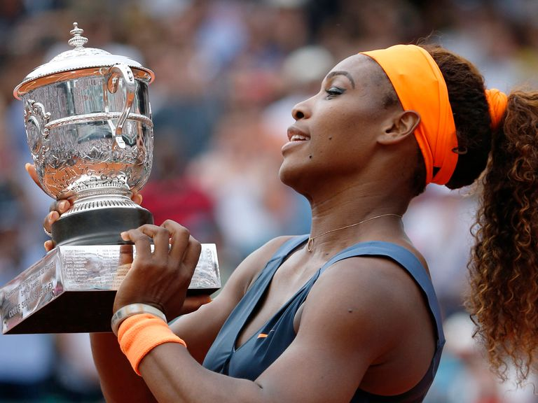 Serena Williams celebrates with the trophy.