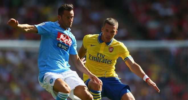 Giandomencio Mesto and Lukas Podolski: Battle for the ball at the Emirates Cup