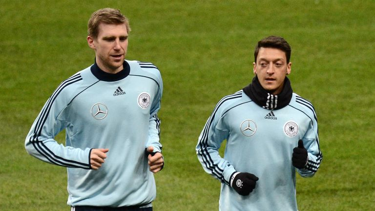 Per Mertesacker (l): Says Mesut Ozil has settled into his new life at Arsenal very quickly