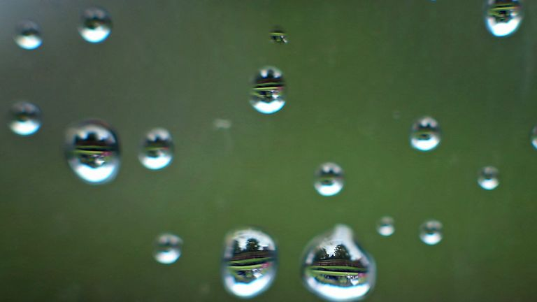 A view of the drenched course is reflected through raindrops on a window