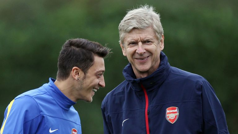 Mesut Ozil and Arsene Wenger share a joke during training