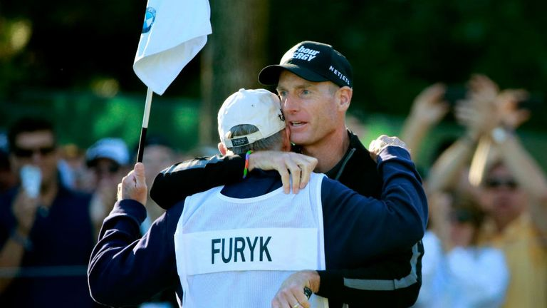Jim Furyk celebrates with caddie Fluff Cowan after holing out at the ninth