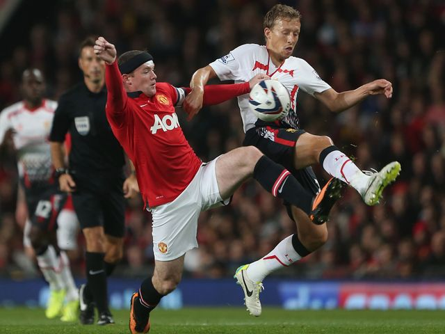 Wayne Rooney tangles with Lucas.
