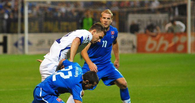 Bosnia's Edin Dzeko gets in a tangle