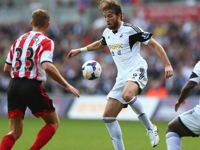 Michu brings the ball down under pressure from Lee Cattermole