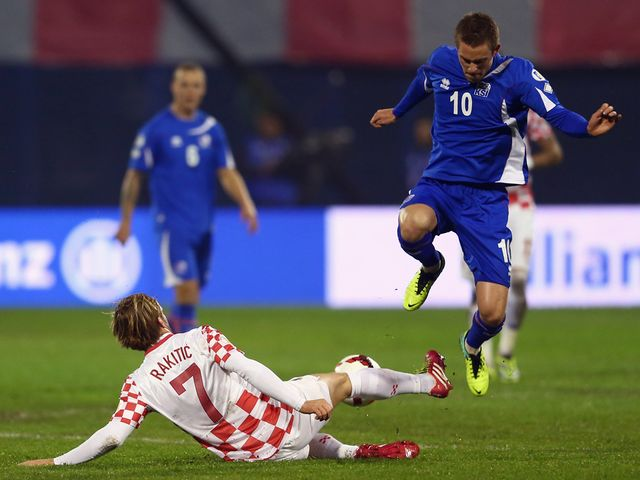 Gylfi Sigurdsson is challenged by Ivan Rakitic.