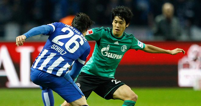 Atsuto Uchida and Nico Schulz battle for the ball