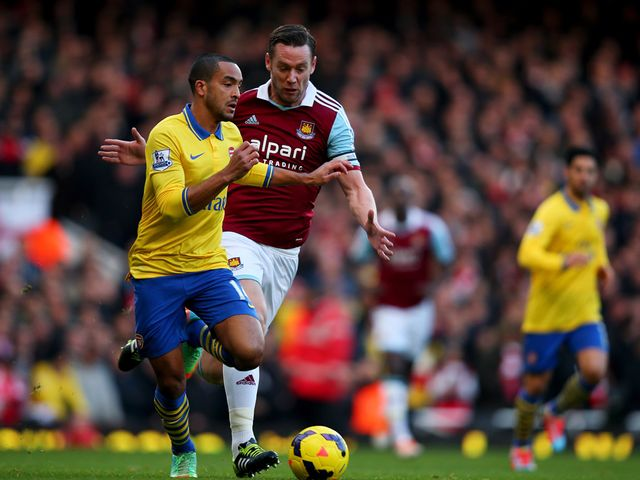 Theo Walcott and Kevin Nolan battle for the ball