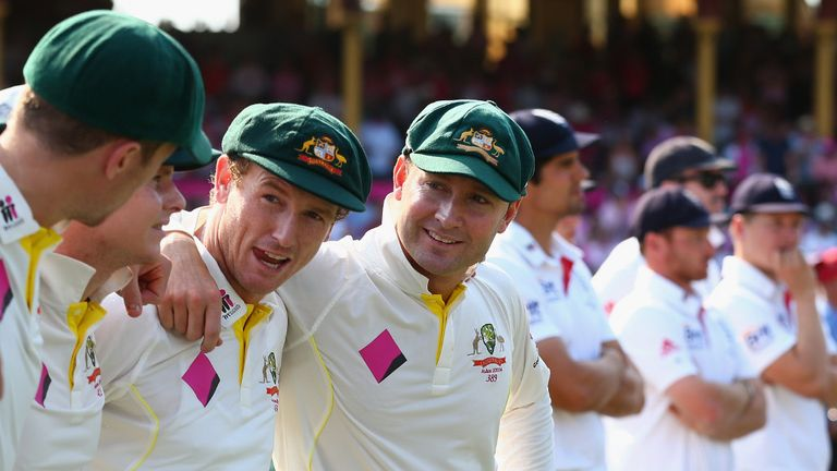Michael Clarke (centre) in buoyant mood, whilst England mull a crushing defeat in background