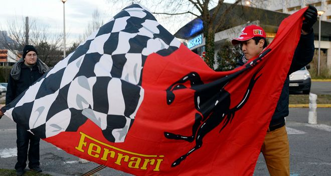 Ferrari fans hold a flag outside the hospital in Grenoble