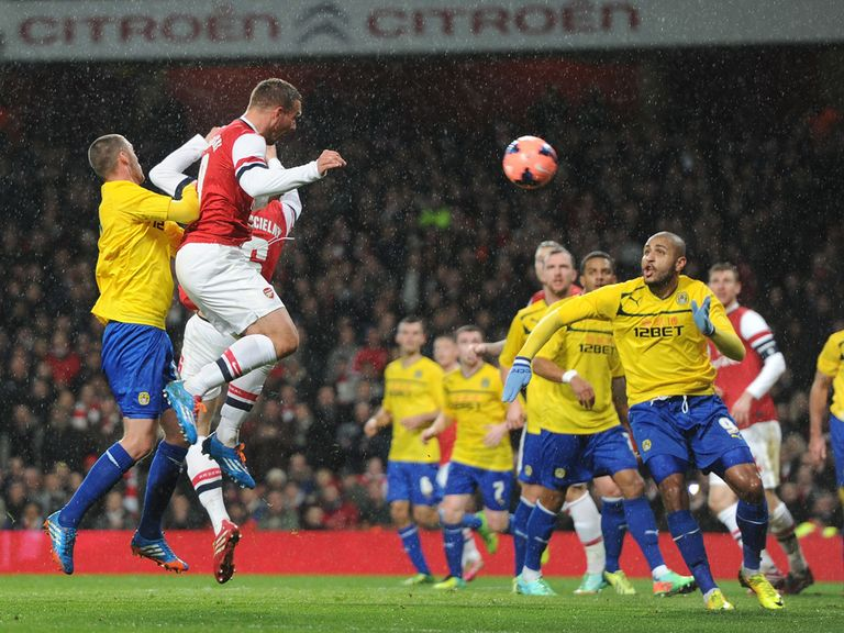 Lukas Podolski heads home as Arsenal beat Coventry 4-0.