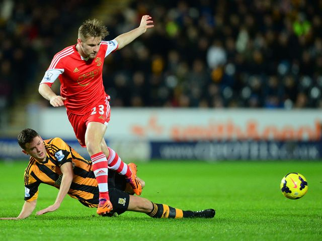 Alex Bruce slides in to tackle Luke Shaw