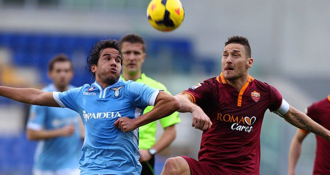Alvaro Gonzalez competes for the ball with Francesco Totti