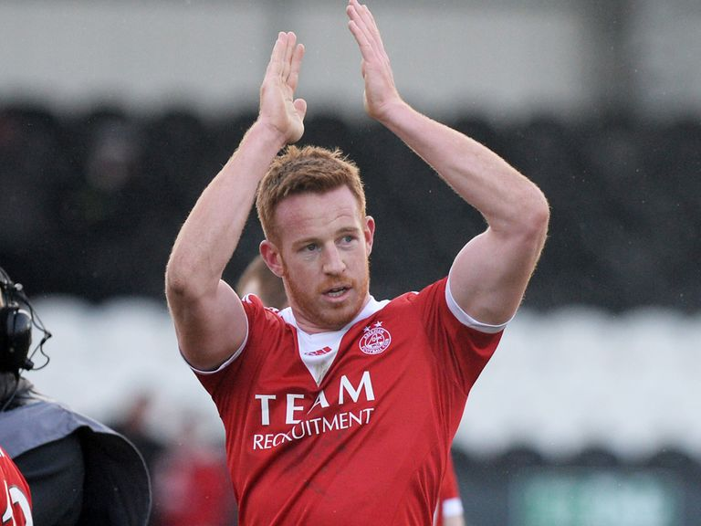 Adam Rooney applauds the fans at the end of the match