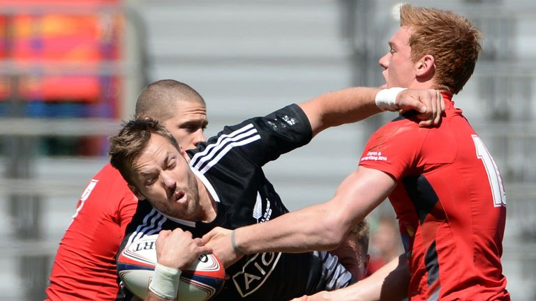 New Zealand's Tim Mikkelson is tackled by James Davies and Sam Cross of Wales