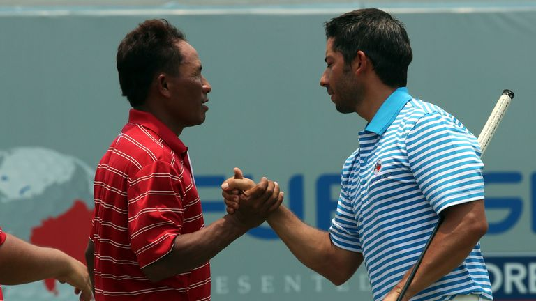 Thongchai Jaidee of Team Asia shakes hand with Pablo Larrazabal of Team Europe on the 18th hole