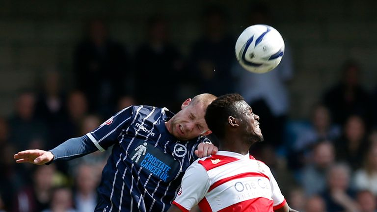 Millwall's Alan Dunne heads away from Doncaster's Theo Robinson