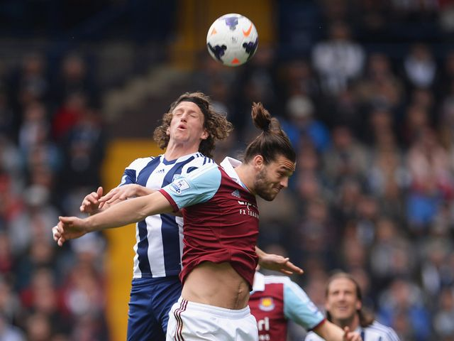 Andy Carroll of West Ham United is challenged by Billy Jones