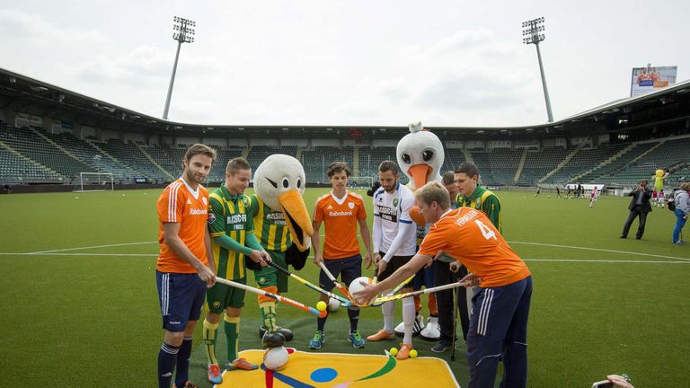 Dutch hockey internationals pose alongside mascots at the Kyocera stadium ahead of the World Cup in The Hague