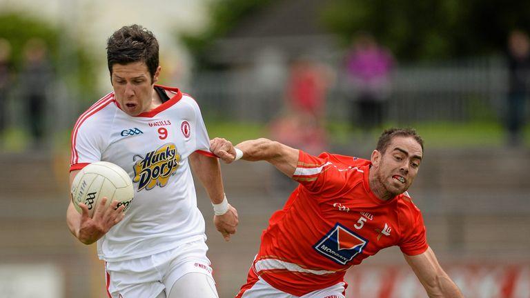Tyrone captain Sean Cavanagh is challenged by John O'Brien