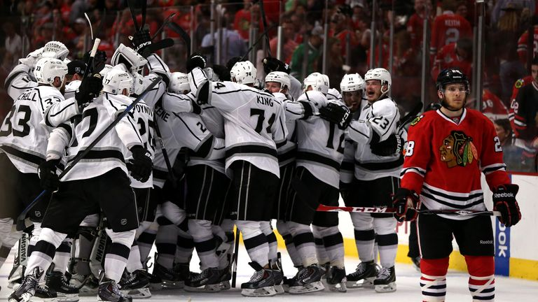 Ben Smithof the Chicago Blackhawks skates away as the Los Angeles Kings celebrate their overtime win