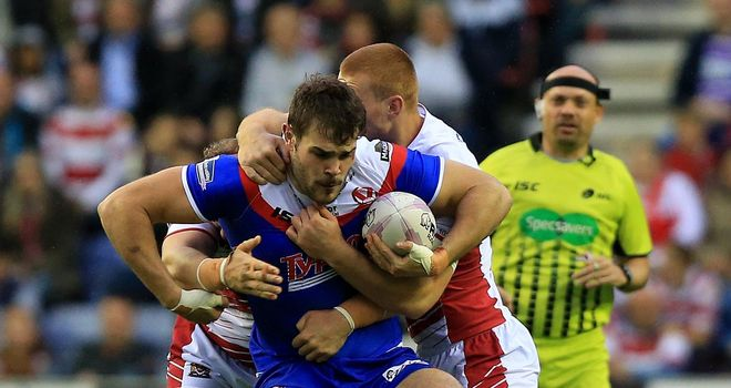 St Helens' Alex Walmsley is tackled by Wigan Warriors' Jack Hughes