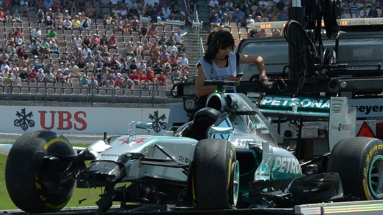 Lewis Hamilton's car is transported back to the garage after crashing during qualifying