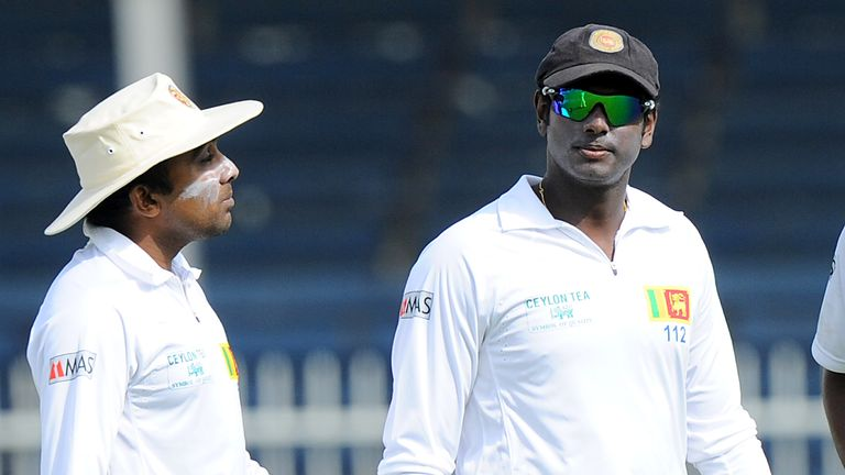 Sri Lankan cricketer Mahela Jayawardene (L) speaks with team captain Angelo Mathews during the third day of the third and final cricket Test match between