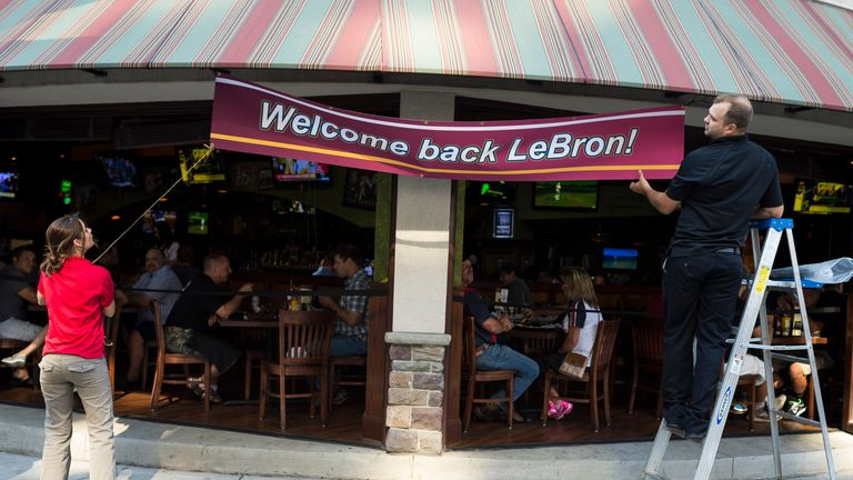 Employees of The Tilted Kilt  in Cleveland hang a banner to welcome back LeBron James